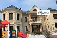 Фасад частного дома с обрамлением окон и дополнительными декоративными элементами