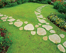 Дорожка из камня в газоне.