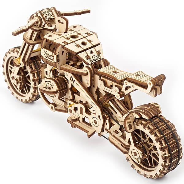 Перед вами легендарный байк, способный покорить любые дороги и даже бездорожье! Подвеска с увеличенным ходом, высоко поднятый глушитель, идеальный баланс: разработчики UGEARS аккуратно скопировали все особенности настоящих скрамблеров, подарив своей модели тот самый Дух Свободы.  «Мотоцикл Scrambler UGR-10 с коляской» – это:      380 деталей, каждая из которых идеально пригнана к соседним. Всё собирается без клея и инструментов, прямо из коробки;     Оригинальная маятниковая подвеска на обоих колёсах – модель получилась даже устойчивее оригинала;     Мощный оппозитный резинодвигатель, способный отправить ваш мотоцикл на 3.5 метра без подзавода!     Стильный ретро-дизайн с открытыми элементами, позволяющими наблюдать за работой мотора в реальном времени;     Вместительная съёмная коляска для пассажиров или небольших грузов: хотите оригинально передать коллеге ластик? Теперь вы знаете, как это сделать!  И пусть у вас нет возможности всё бросить и прямо сейчас отправиться в путешествие по дорогам мира, «Мотоцикл Scrambler UGR-10 с коляской» от UGEARS поможет развеять ежедневную скуку и дождаться следующего отпуска!