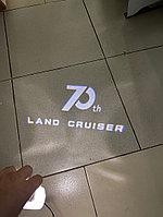 Проекция под дверь с надписью 70th на Land Cruiser 300